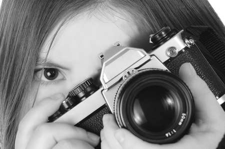 A woman positions a camera for a shot. One eye is visible. Black and white. Imagens