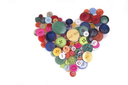 sew: Een hart gevormd met kleurrijke knoppen geïsoleerd tegen een witte achtergrond. Stockfoto