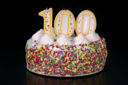 centenarian: Un colorido pastel de cumplea�os con velas de forma, tales como el n�mero 100. Fondo negro.