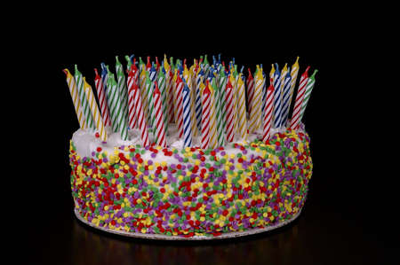 A birthday cake with a myriad of candles. Black background.