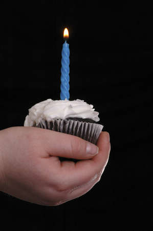 A hand holding a cupcake with one blue candle in it. The candle has been lit. Black background.