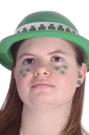 A smiling woman with green shamrocks on her cheek.