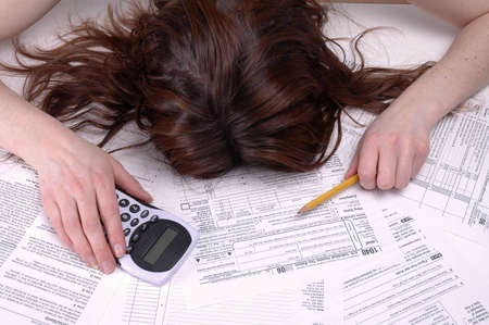 A woman slumped over in despair on a pile of tax forms. photo