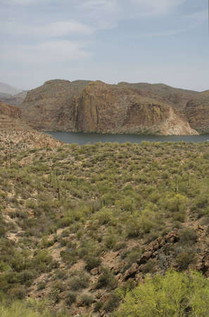 A lake in the distance contrasts with a desert landscape.