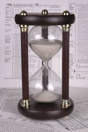 An hour glass rests on tax forms. More tax forms serve as the background. Stock fotó
