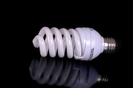 A fluorescent light bulb against a black background. Imagens