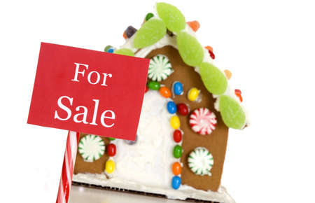 A For Sale sign in front of a gingerbread house. Shallow depth of field. Focus is on the sign. Imagens