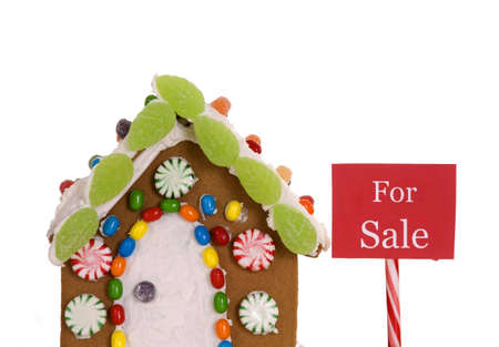 gingerbread house: A For Sale sign next to a gingerbread house.
