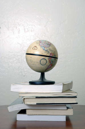 A world globe sitting on a pile of books. North and South America are visible. Imagens