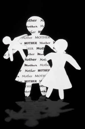 A mother, little girl, and baby made from paper against a black background. Stock fotó