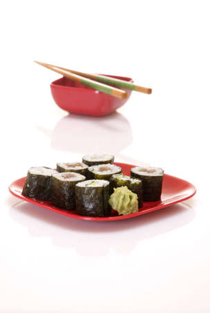A plate of sushi in the foreground with an out of focus dish of soy sauce in the background.