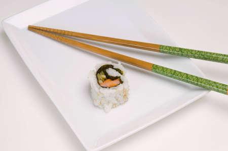 하얀 접시에 초밥의 단일 조각입니다. 흰색 배경.