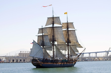 buccaneer: An old-fashioned sailing ship sails past a modern city  Stock Photo
