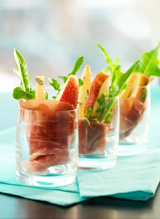antipasto: appetizer with pear,prosciutto,arugula,gorgonzola in glasses Stock Photo