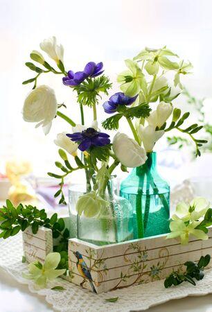 ranunculus:  ranunculus, anemone, freesia and hellebore in glass bottles