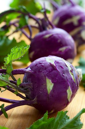 fresh purple kohlrabi with leaves on a wooden table photo