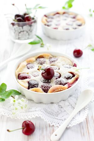 Cherry Clafoutis with powdered sugar in baking dishes photo