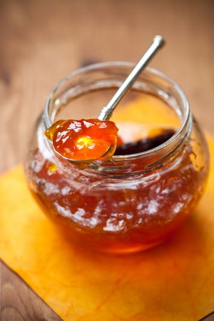 orange jam with cinnamon in jar with spoon