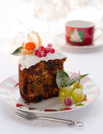 sugared: slice of  Christmas fruit cake with white frosting and sugared fruits Stock Photo