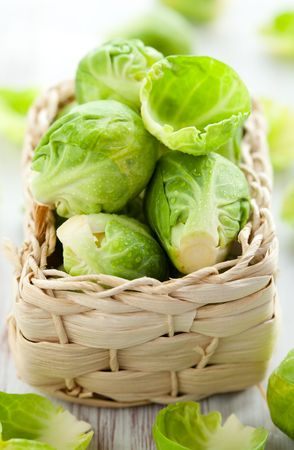 sprouts: Wet brussels sprouts in basket on the white wooden table Stock Photo