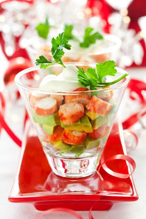 crabmeat: Crab salad with avocado in two glasses . Served on a Christmas table.