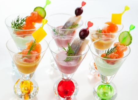 Salmon and herring appetizers in glasses with three different  sauce(mustard,wasabi and cranberry sauce) photo