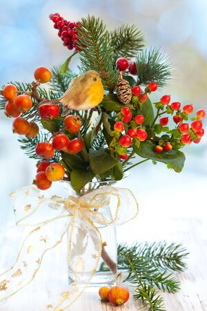 Christmas arrangement of ornamental apples(malus),fir branch and holly in vase Stock Photo - 8115469