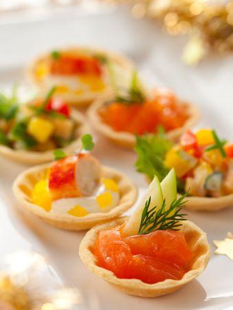 Weihnachten Vorspeise Teller mit appetizers.Tartlets mit drei unterschiedlichen Füllungen (Gemüsesalat, Krabben-Salat und geräucherter Lachs mit Apfel)