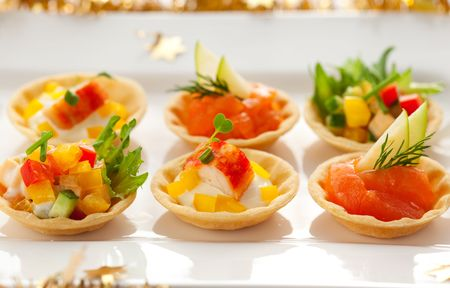 red salmon: Christmas starter platter with appetizers.Tartlets with three different fillings(vegetable salad,crab salad and smoked salmon with apple)