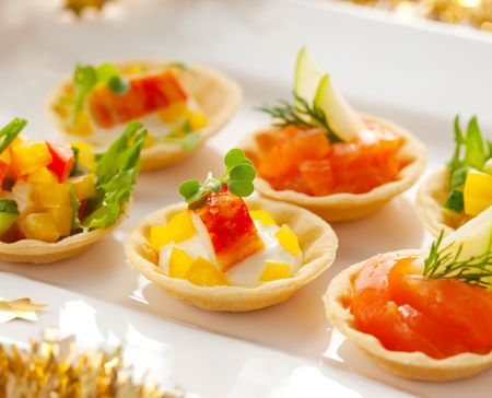 Christmas starter platter with appetizers.Tartlets with three different fillings(vegetable salad,crab salad and smoked salmon with apple) photo