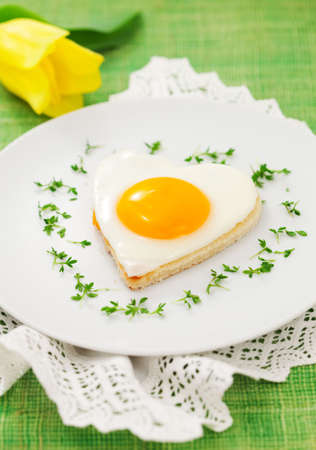 Fried egg on heart-shaped toast with cress and corn salad for Valentines Day photo