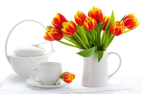 desayuno romantico: Tulipanes rojos en una jarra y una taza de té en blanco Foto de archivo