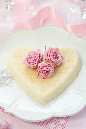 blancmange: Heart-shaped ricotta dessert with candied roses for Valentines Day Stock Photo