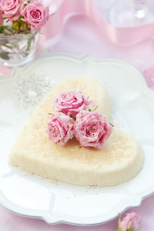 Heart-shaped ricotta dessert with candied roses for Valentines Day photo