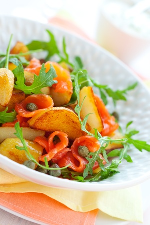 Potato salad with smoked salmon,capers,rocket and sauce photo