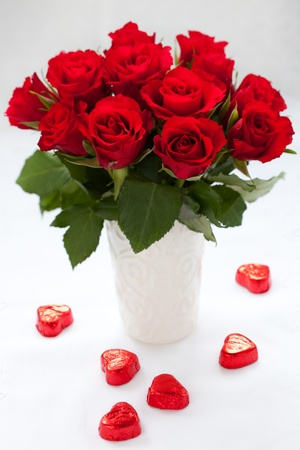 red roses in vase and chocolate candies for Valentines Day photo