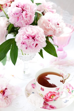 Pink peonies in vase and cup of tea photo
