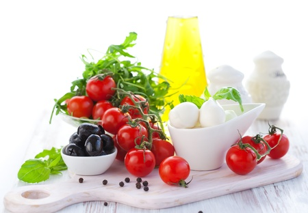 Ingredients for salad  with mozzarella, tomatoes,black olives,rocket and olive oil photo