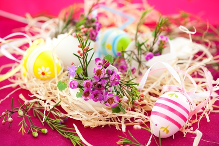 Easter decoration: nest with spring pink flowers in eggshells photo