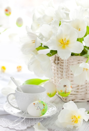 white tulips,cup of tea and easter eggs photo