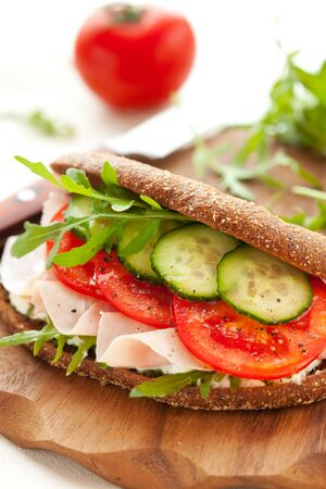 arugula: Sandwich with ham,tomato, cucumber and arugula on the wooden cutting board