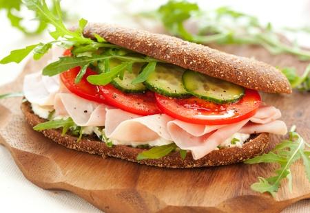 ハム、トマト、キュウリ、木製のまな板にルッコラのサンドイッチ