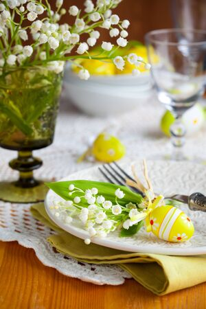 Easter table with  lily-of-the-valley and eggs photo
