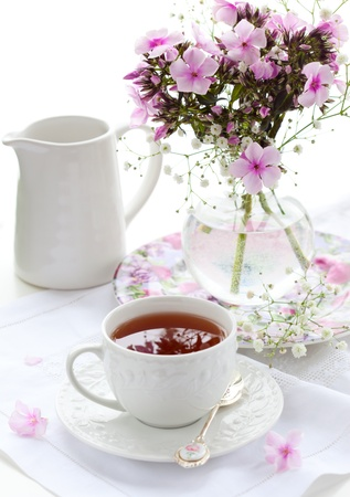 cut flowers: A cup of black tea  and phloxs in vase