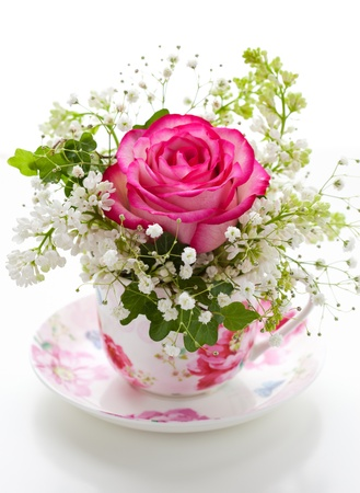vase color: Pink rose and white lilac in a cup