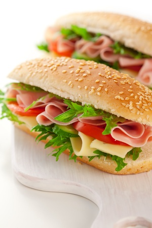 sandwich: s�ndwich de jam�n, queso y verduras sobre fondo blanco Foto de archivo