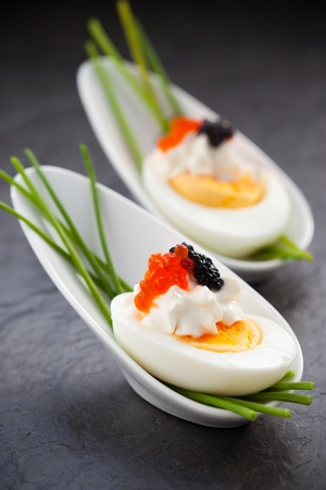 Boiled eggs with red and black  caviar in  spoon photo