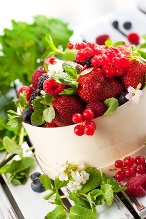 fresh berries with leaves in a wooden basket photo