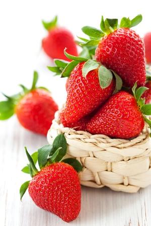 fresa: de fresas frescas en una cesta de una tabla de madera blanca Foto de archivo