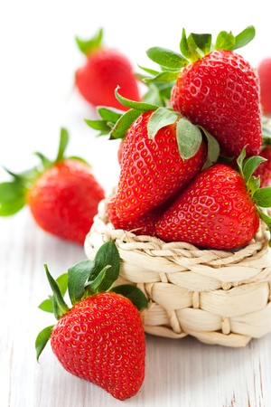 fresh strawberries in a basket on a white wooden table Stock Photo